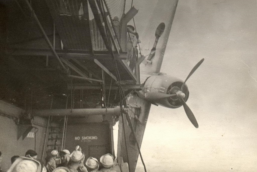 USS Sable (IX 81) showing a TBF hanging over the side after crashing during carrier qualifications on Lake Michigan.