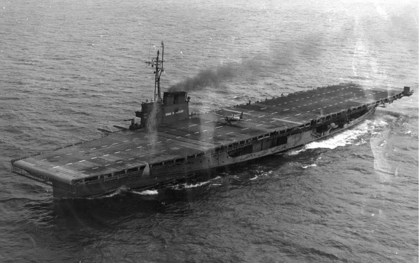 Overhead view of the training aircraft carrier 'Sable' (IX 81) underway on Lake Michigan with an FM Wildcat making a deck launch from the flattop 1945