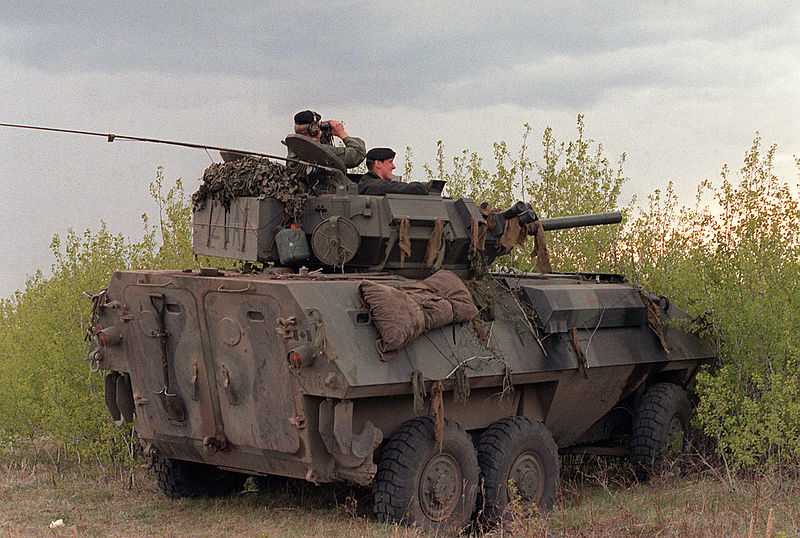 A right rear view of a Canadian army Cougar wheeled fire support vehicle that is being used as an observation post by soldiers standing watch during the combined U.S./Canadian NATO Exercise Rendezvous '83. Location: Camp Wainright, AB