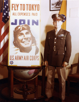 Brig. Gen. James Doolittle poses beside an Air Corps recruiting poster that alludes to his bombing raid on Japan in April 1942. (c) 1943