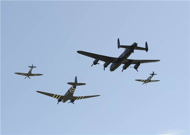 Two Spitfires, a Dakota DC-3, and a Lancaster Bomber conduct a flypast over Juno Beach, France, during commemorative ceremonies of the 70th Anniversary of D-Day on June 6, 2014. Photo by Sgt Bern LeBlanc Canadian Army Public Affairs AS2014-0027-002