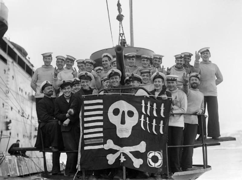 "Members of the crew of HMS Utmost with their ""Jolly Roger"" success flag, photographed alongside HMS Forth in Holy Loch, on their return from a year's service in the Mediterranean, 6 February 1942. (via Wikipedia)"