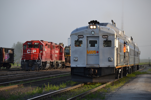 Eastbound train 186, with the RDC baggage car in the lead, passes a CP freight train carrying backhoes at the small White River, ON yard on June 19, approaching the station to begin its run towards Sudbury. (Photo by Malcolm Kenton)